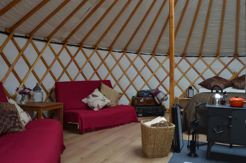 the yurts contain a double bed, 2 double futons, dining table and other furniture