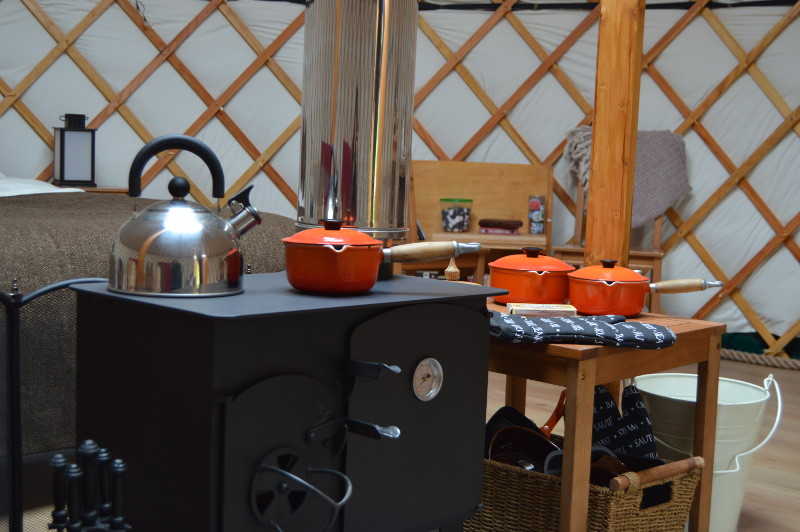the yurt contains a log burning stove which incorporates a hotplate and oven